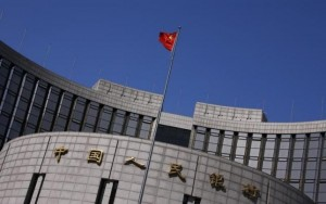 A Chinese national flag flutters outside the headquarters of the People's Bank of China in Beijing