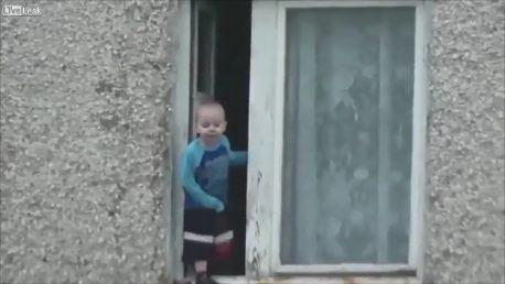 Kid balance on window ledge of Russian high rise
